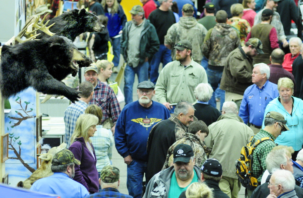 Showgoers walk past a booth with stuffed bears on display Saturday during the State of Maine Sportsman's Show at the Augusta Civic Center.