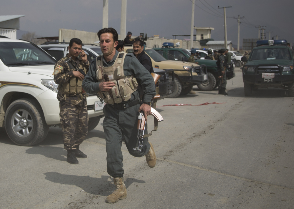 An Afghan police man rushes to the scene as Taliban militants attacked the main Afghan election commission's headquarters in the outskirts of Kabul, Afghanistan, firing on the compound with rocket-propelled grenades and heavy machine guns from a house outside its perimeter wall on Saturday.