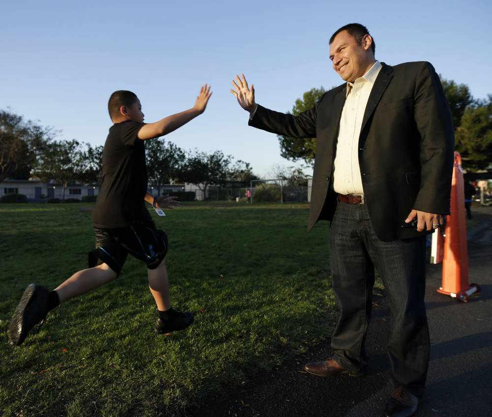 Rice Elementary School Principal Ernesto Villanueva slaps hands with students during an early morning running program in Chula Vista, Calif. Amid alarming national statistics showing an epidemic in childhood obesity, hundreds of thousands of students across the country are being weighed and measured.