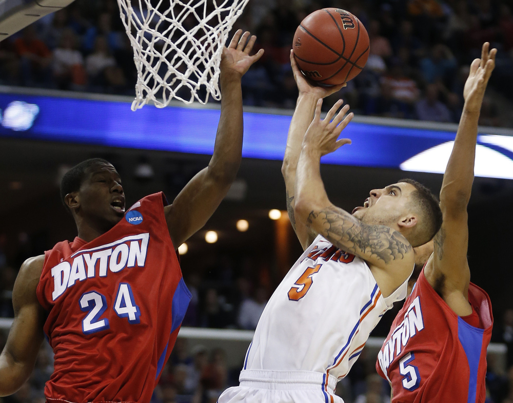 Florida guard Scottie Wilbekin (5) shoots against Dayton guard Jordan Sibert (24) during the second half in a regional final game at the NCAA college basketball tournament, Saturday, in Memphis, Tenn.