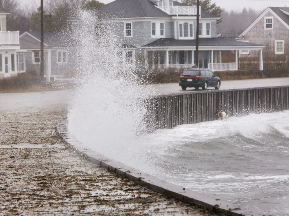 A car drives along Beach Avenue in Kennebunk on Sunday, as a wave hits a seawall, splashing water onto the sidewalk.