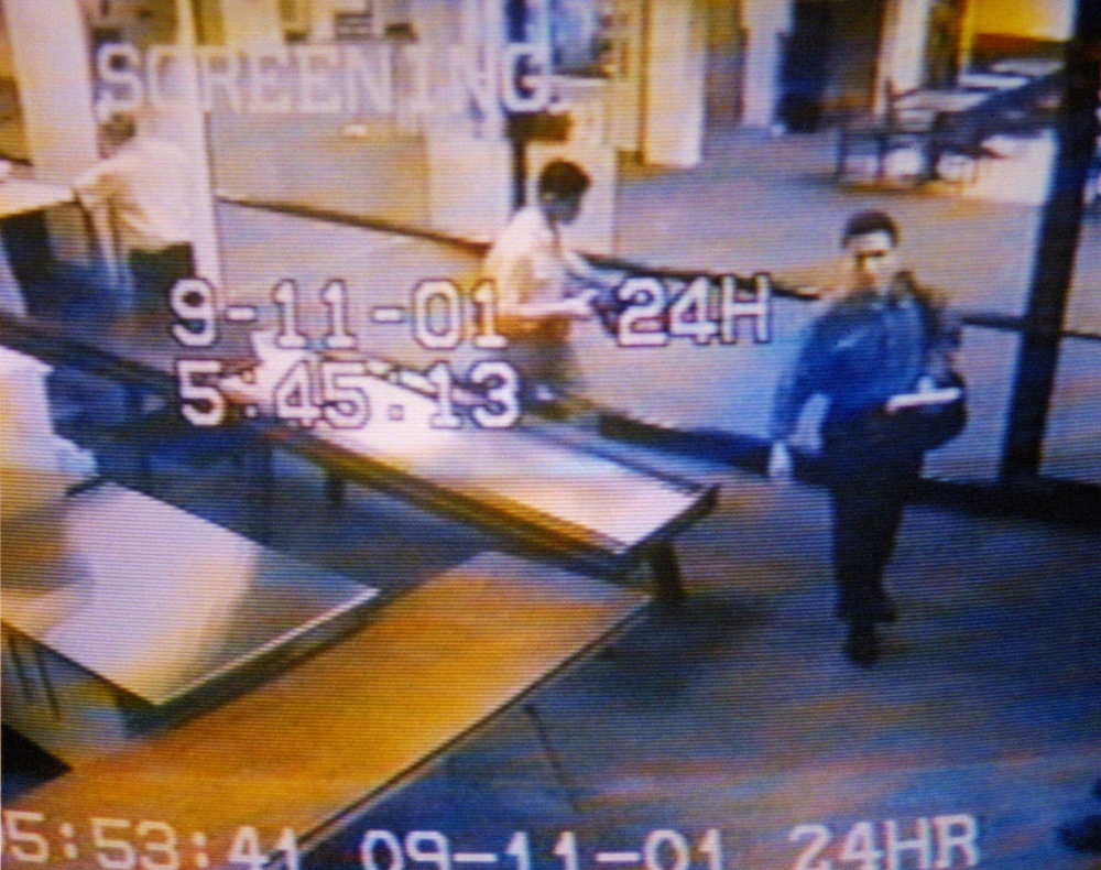Mohamed Atta, right, and Abdulaziz Alomari, center, pass through airport security at the Portland jetport to catch a commuter flight to Boston on the day of the Sept. 11 attacks.