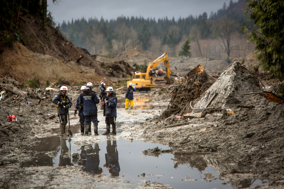 As rain adds to the danger, rescue workers continue to search the muck and debris left by the Oso mudslide along State Route 530 near Darrington, Wash.