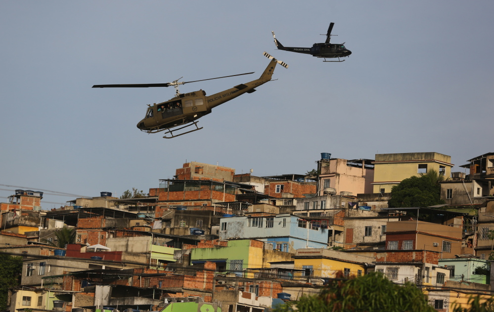 "Police helicopters fly over the Mare slum complex in Rio de Janeiro, Brazil, on Sunday as 14,000 police and Marines move in on the area. The operation is part of a ""pacification effort that began in 2008 to secure Rio before this year's World Cup."