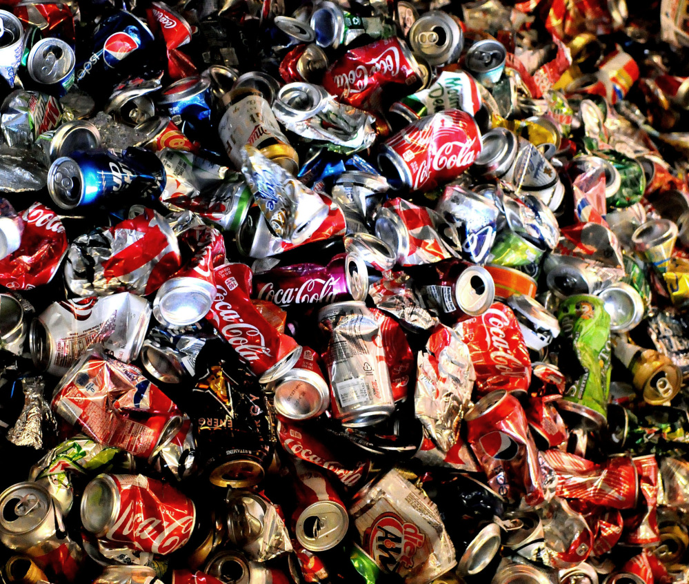 Empty and crushed soda cans build up on a conveyer belt near the end of the line at Tennis Sanitation in Saint Paul Park, Minn. Americans cut back on soda again in 2013, extending a trend that began nearly a decade ago.