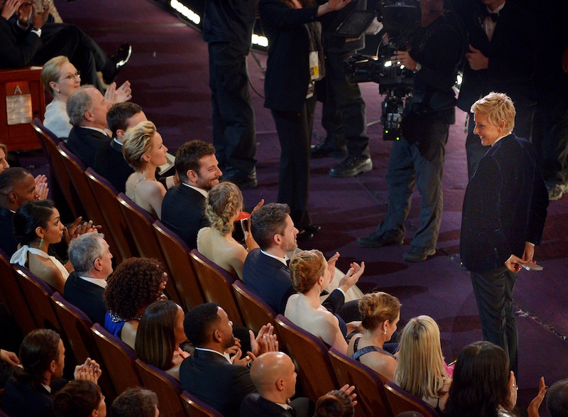 Ellen DeGeneres, right, stands in the audience during the Oscars at the Dolby Theatre on Sunday, March 2, 2014, in Los Angeles.