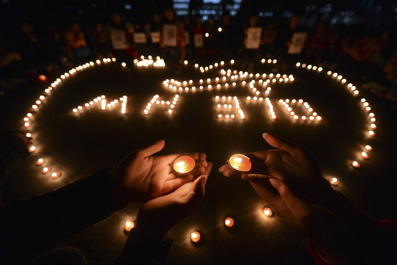 In this Thursday March 13, 2014 photo, university students hold a candlelight vigil for passengers on the missing Malaysia Airlines Flight MH370 in Yangzhou, in eastern China's Jiangsu province. China on Friday urged Malaysia's government to release any information it has regarding the missing Malaysia Airlines jetliner to help narrow the search area.