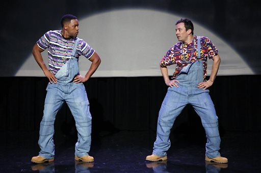 In this image released by NBC, Will Smith, left, and host Jimmy Fallon act out the evolution of hip-hop dancing on the premiere of