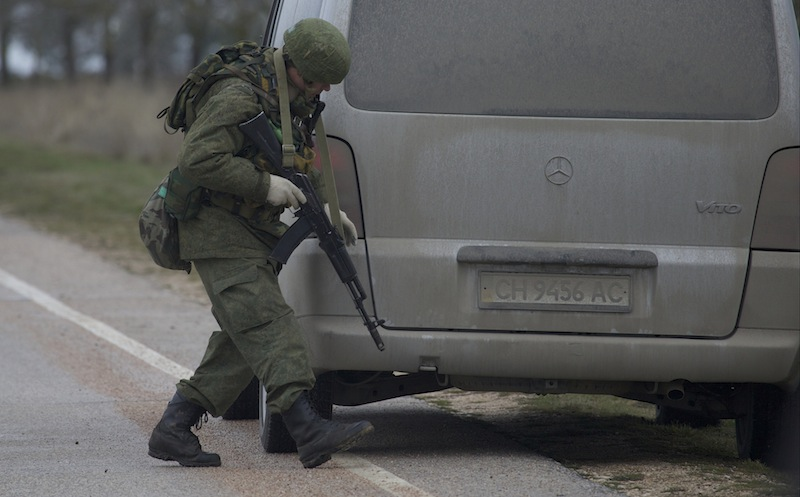 An unidentified gunman searches a vehicle while he and others block the road toward the military airport at the Black Sea port of Sevastopol in Crimea, Ukraine, Friday, Feb. 28, 2014. Russian troops took control of the two main airports in the strategic peninsula of Crimea, Ukraine's interior minister charged Friday, as the country asked the U.N. Security Council to intervene in the escalating conflict. Russian state media said Russian forces in Crimea denied involvement. No violence was reported at the civilian airport in Crimea's capital of Simferopol or at the military airport in the Black Sea port of Sevastopol, also part of Crimea.