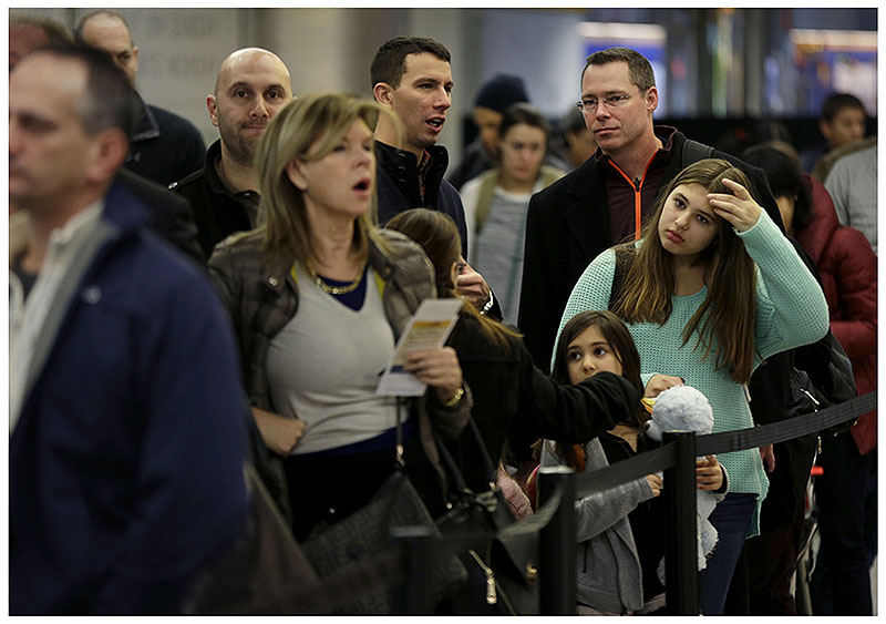 Coach passengers wait in line to board a flight at LaGuardia Airport in New York.