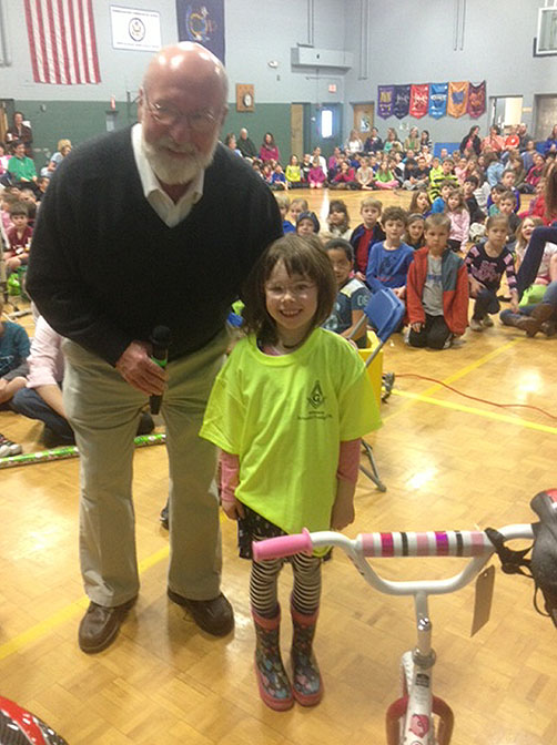 Larry Vennell of the Free Mason Arundel Lodge Post No. 76 and kindergartener Lillian Lavery of the Kennebunkport Consolidated School with one of the 22 bicycles raffled off as prizes for students who participated in a literacy initiative at the school.