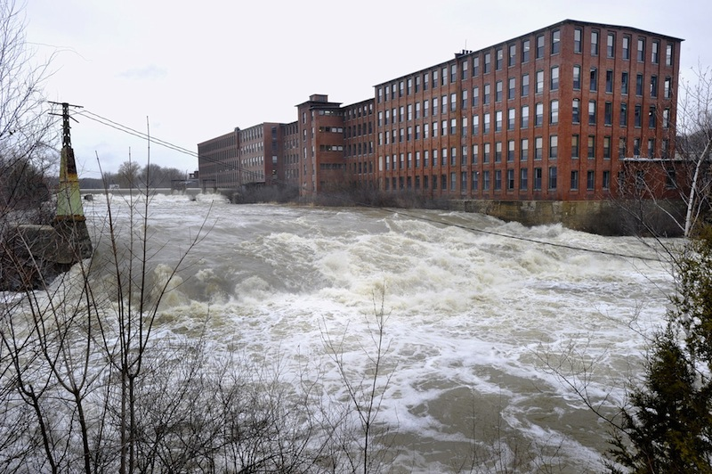 In this December 2010 file photo, high water on the Presumpscot River flows over Westbrook's Saccarappa Falls. Environmental and city officials have an agreement with Sappi Fine Paper that gives the company a two-year extension of a 2015 deadline to construct a fish passage at the Saccarappa Falls dam on the Presumpscot River.