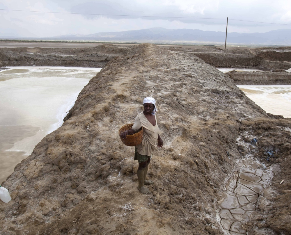 A worker suffering from heat exhaustion leaves her shift early at the salt evaporation ponds in Haiti as drought has hit the region, one of the hungriest, most desolate parts of the nation.