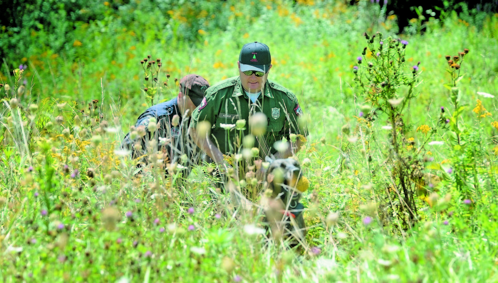 Lt. Kevin Adams, foreground, of the Maine Warden Service, Trooper Shawn Porter, of the Maine State Police, and search dog Myka emerge from the woods Aug. 27 near Skowhegan's Reddington-Fairveiw General Hospital on Fairview Avenue shortly after finding the body of Vaughn Giggey.