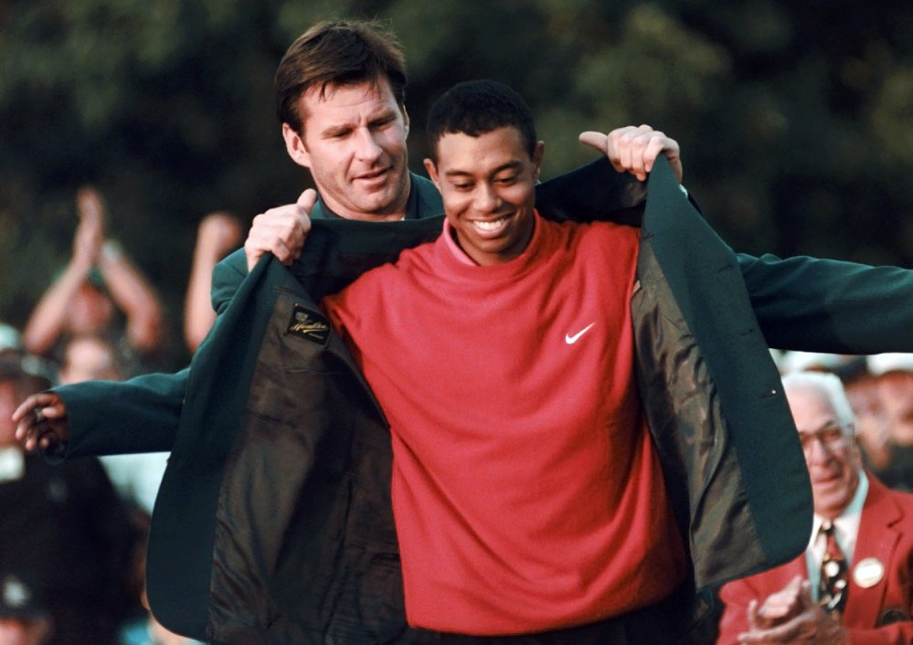 In this April 13, 1997, photo, Masters champion Tiger Woods receives his green jacket from the previous year's winner, Nick Faldo, at the Augusta National Golf Club in Augusta, Ga.