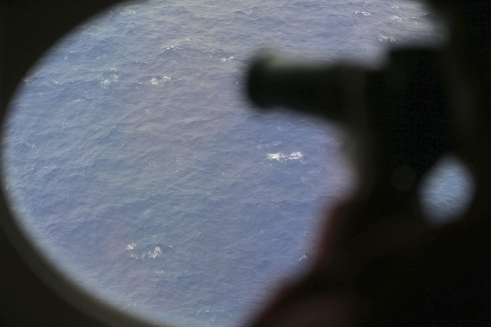An observer on a Japan Coast Guard Gulfstream aircraft takes photos out of a window while searching for the missing Malaysia Airlines Flight MH370 in Southern Indian Ocean, near Australia, Tuesday, April 1, 2014. Bad weather and poor visibility caused the search to be called off early with the coast guard plane only completing one of its three 210 nautical mile legs.