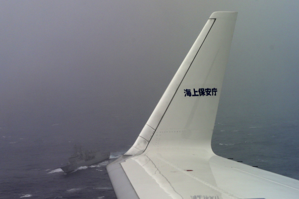 "A Japan Coast Guard Gulfstream aircraft flies past HMAS Toowoomba as they both conduct searches for the missing Malaysia Airlines Flight MH370 in Southern Indian Ocean, near Australia, Tuesday, April 1, 2014. Bad weather and poor visibility caused the search to be called off early with the coast guard plane only completing one of its three 210 nautical mile legs. The letters in the winglet read: ""Coast Guard."""