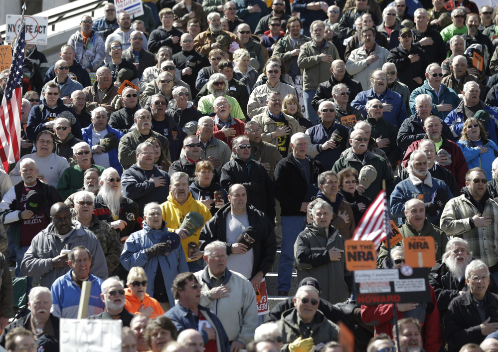 Gun rights activists recite the Pledge of Allegiance Tuesday during a rally at the Empire State Plaza in Albany, N.Y. They were protesting a restrictive 2013 gun law and new gun control proposals announced Tuesday.