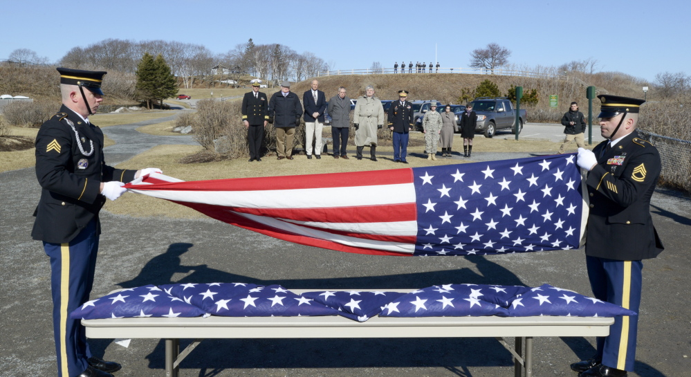 Sgt. David Chabe and Sgt. 1st Class Norman Voter fold one of eight flags to be presented to descendants, standing at back, of George Osborn Sr. who served with his seven sons in the Revolutionary War.