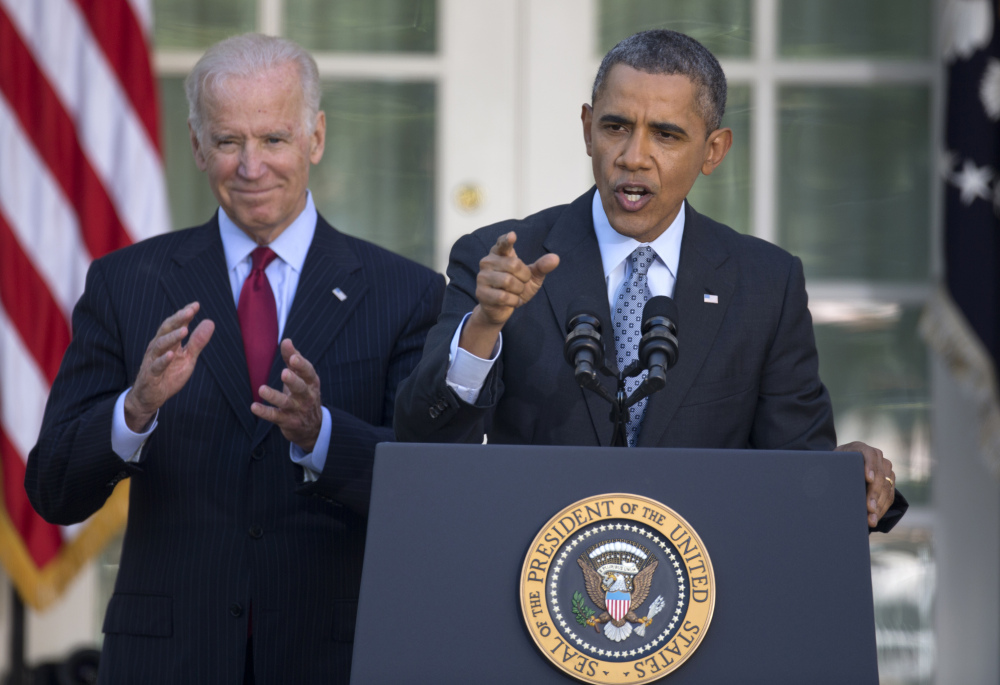 President Barack Obama, with Vice President Joe Biden, speaks in the Rose Garden of the White House in Washington on Tuesday, the day after the deadline to sign up for health insurance under the Affordable Care Act.
