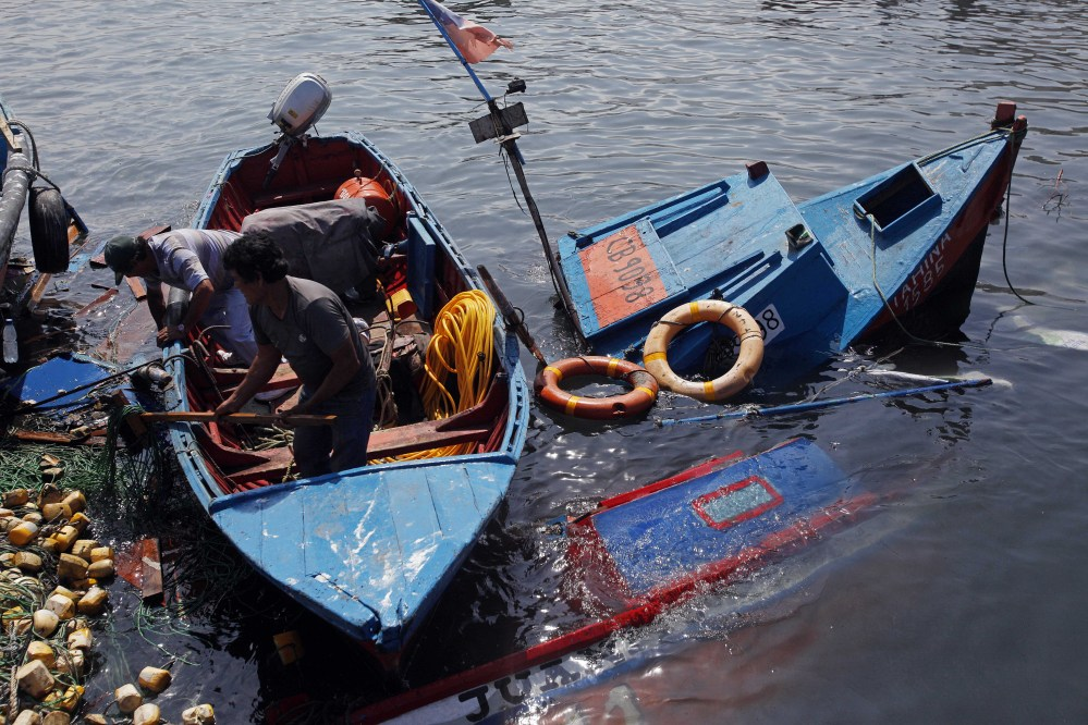 Fishermen salvage remains destroyed overnight in the port of Iquique, Chile, Wednesday.
