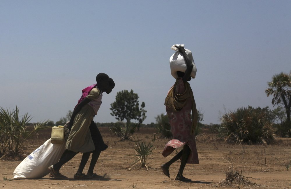 Women carry food distributed in Nyal in South Sudan on Tuesday. Air drops of food are three times more expensive than road deliveries but crucial in the inaccessible area.