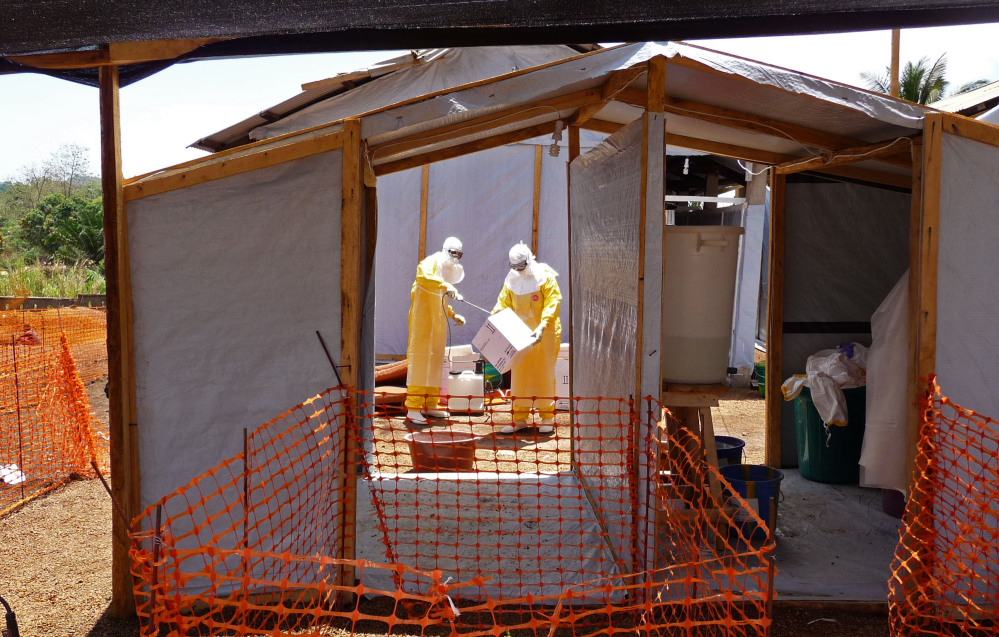 In this photo provided by Doctors without Borders, taken on Friday, March 28, 2014, health care workers from the organisation prepare isolation and treatment areas for their Ebola hemorrhagic fever operations, in Gueckedou, Guinea.