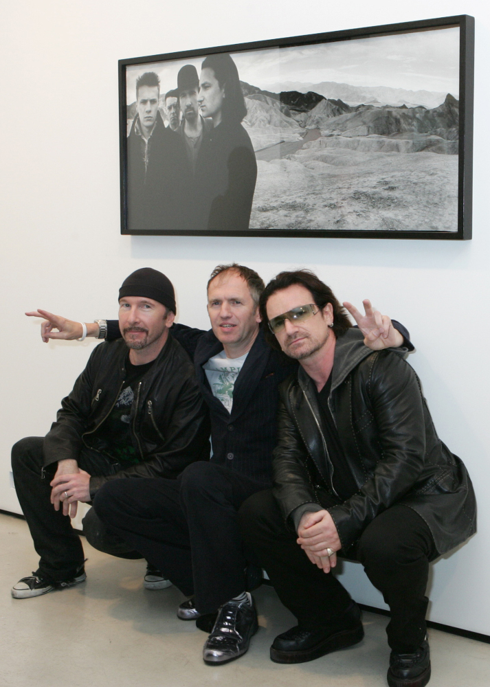 U2's Bono, right, and guitarist The Edge, left, pose with photographer Anton Corbijn in New York, under a portrait of the band from the Joshua Tree album cover, in gthis 2005 photo.