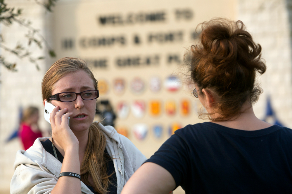 Krystina Cassidy, left, and Dianna Simpson attempt to make contact with their husbands who are stationed inside Fort Hood while standing outside of the Bernie Beck Gate on Wednesday, April 2, 2014, in Fort Hood, Texas. At least one person was killed and 14 injured in the shooting, and officials at the base said the shooter is believed to be dead.