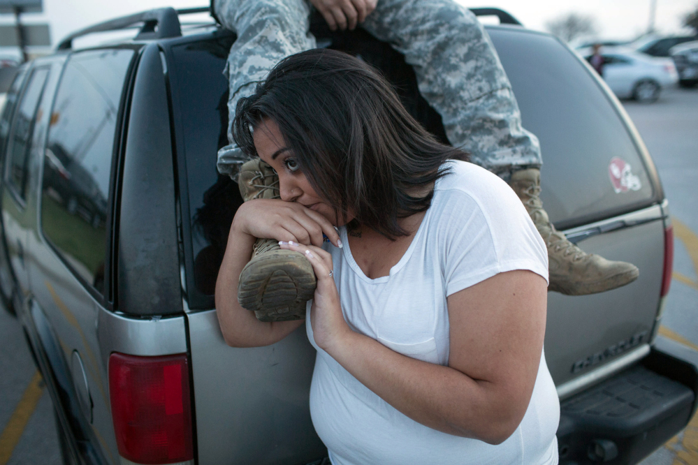 Lucy Hamlin and her husband, Spc. Timothy Hamlin wait for permission to re-enter the Fort Hood military base, where they live, following a shooting on base on Wednesday, April 2, 2014, in Fort Hood, Texas. One person was killed and 14 injured in the shooting, and officials at the base said the shooter is believed to be dead. The details about the number of people hurt came from two U.S. officials who spoke on condition of anonymity because they were not authorized to discuss the information by name.