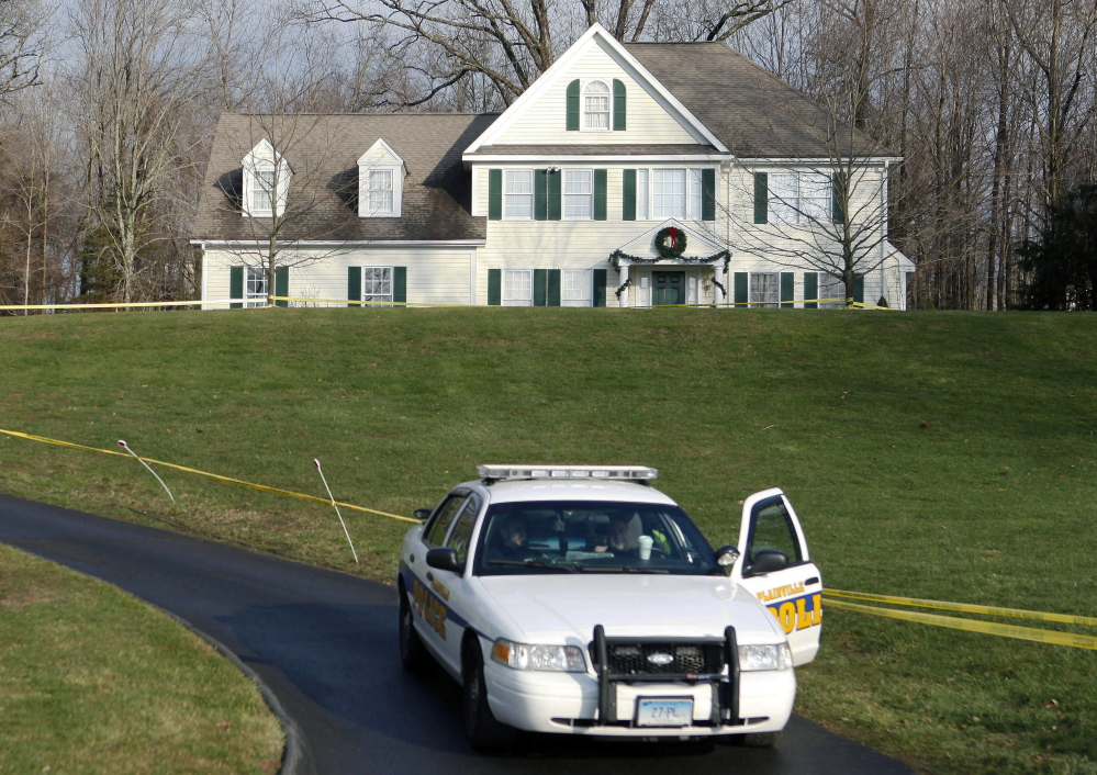 In this 2012 photo, a police cruiser sits in the driveway as crime scene tape surrounds the home of Nancy Lanza in Newtown, Conn.