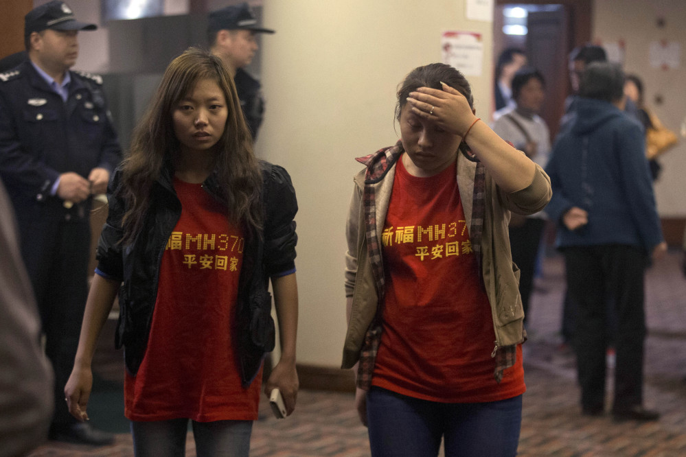 "Relatives of the Chinese passengers onboard the Malaysia Airlines flight MH370 wear T-shirts with the words ""Pray for MH370, safe return"" in Beijing Thursday, April 3, 2014. No trace of the Boeing 777 has been found nearly a month after it vanished in the early hours of March 8 on a flight from Kuala Lumpur to Beijing with 239 people on board."