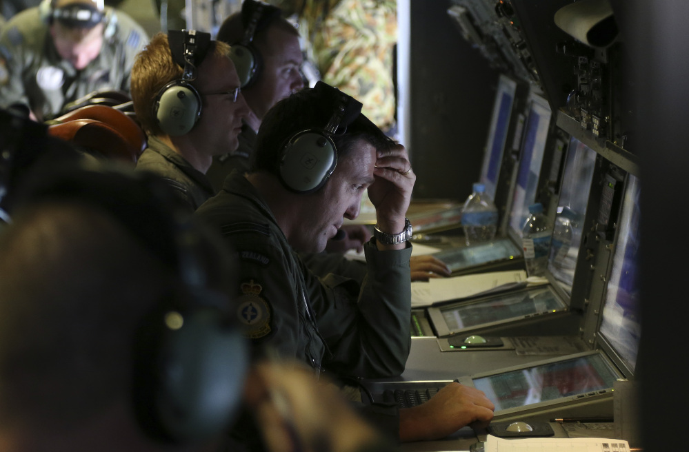Operators monitor operations aboard a Royal New Zealand Air Force P3 Orion during the search for wreckage and debris of missing Malaysia Airlines Flight MH370 in the southern Indian Ocean, near the coast of Western Australia, on Friday.