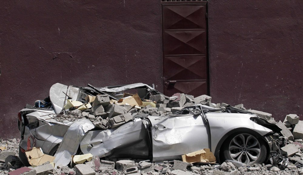 Debris from a magnitude-8.2 quake covers a car Friday in Iquique, Chile. The city remained largely peaceful.