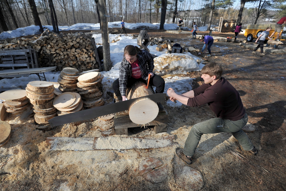 Chris Krasniak, 20, works the buck saw as Tara Chizinski, 21, oils the saw and wedges the disc during timber sports practice at Colby College on Thursday.