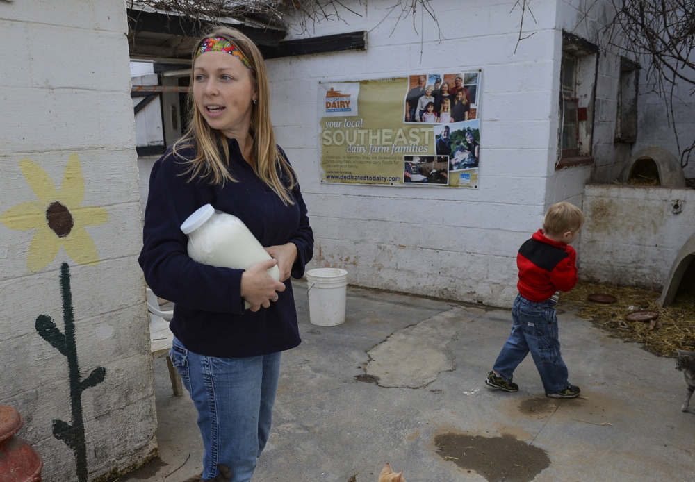 Jen Bernick and her son Solomon, 4, of Winchester pick up a gallon of raw milk at the farm.