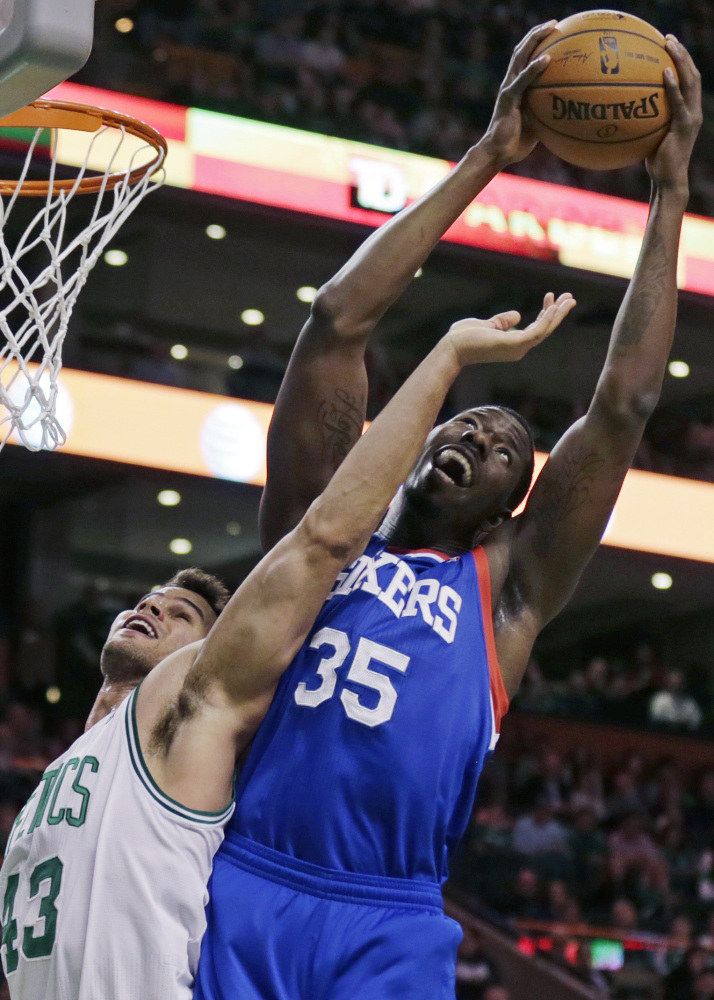 Henry Sims of the Philadelphia 76ers, right, hauls down a rebound over Kris Humphries of the Boston Celtics during the first quarter of the 76ers' 111-102 victory Friday night at Boston.