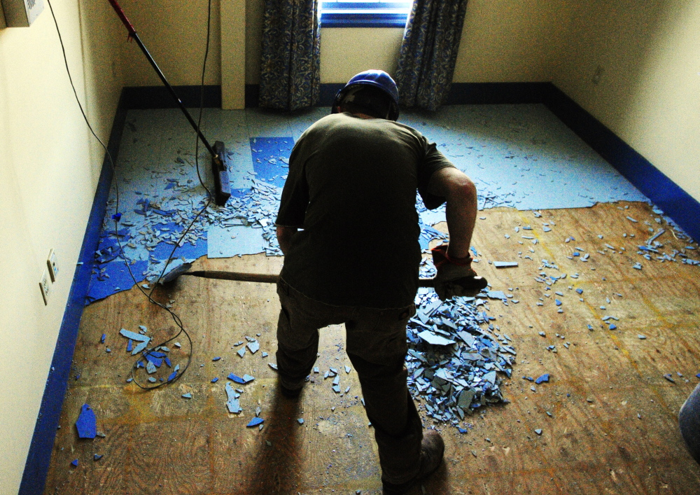 MacKenzie Dunton, of Peachey Builders, chips tiles off the floor in the Haynes Building at the corner of St. Catherine and East Chestnut Streets, left, just up hill from the old MaineGeneral Medical Center on Friday in Augusta.