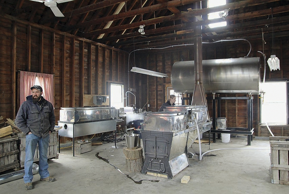 Jim Lattanzi, co-owner of the Hollis Hills Farm in Fitchburg, Mass., talks about the farm's maple syrup production, as his wife, Allison, checks new equipment in their sugar house. The farmers are expanding after buying another farm in Fitchburg.
