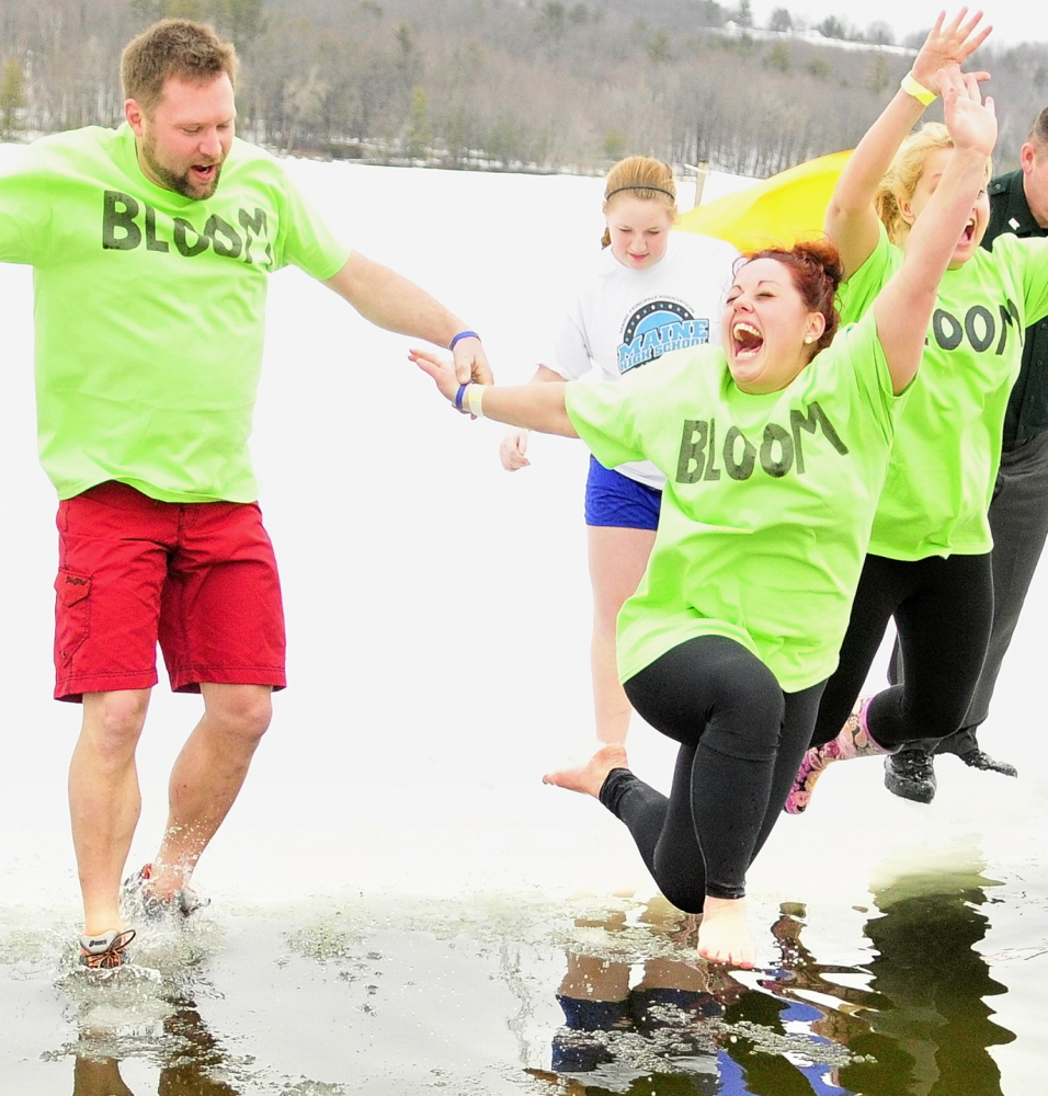 Green-shirted Team Bloom members Corey Rubchinuk, left, Kayla Diplock and Kim Stoenton leap into Maranacook Lake during the Ice Out Plunge on Saturday in Winthrop.