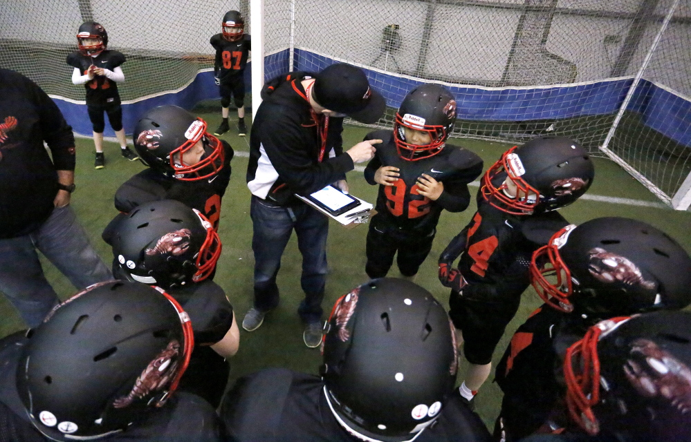 Head coach Skip Winter, center, talks to Mark Erinna, at right, and other Seacoast Lobsters players during a winter practice in York. The youth team's eight coaches teach heads-up tackling to try to prevent concussions.