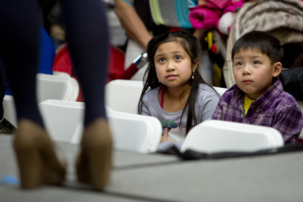 SOUTH PORTLAND, ME - APRIL 5: Brianna Nguyen, 9, and Kevin Tran, 5, of Westbrook, watch a model walk the runway during a fashion show put on by the Portland Arts & Technology High School's fashion marketing students at the Maine Mall in South Portland Saturday, April 5, 2014. (Photo by Gabe Souza/Staff Photographer)