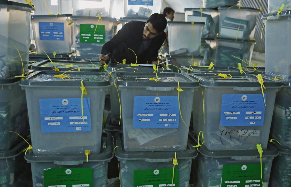 An Afghan elections worker notes serial numbers on ballot boxes at an official elections warehouse in Kabul, Afghanistan on Sunday, as trucks and donkeys loaded with ballot boxes made their way to counting centers.