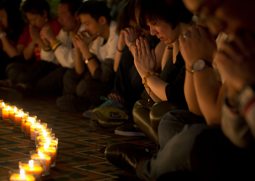 Relatives of Chinese passengers onboard Malaysia Airlines Flight 370 pray during a candlelight vigil for their loved ones at a hotel in Beijing, China on Tuesday, April 8.