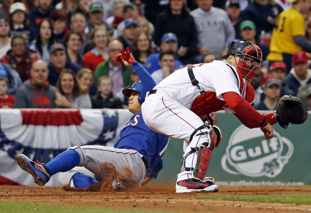 Texas Rangers' Shin-Soo Choo scores on a double by Prince Fielder as Boston Red Sox catcher A.J. Pierzynski waits for the ball in the third inning of a baseball game at Fenway Park in Boston, Tuesday, April 8, 2014.