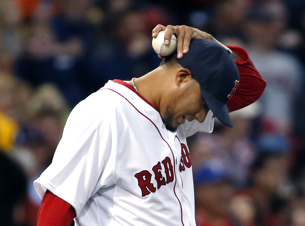Boston Red Sox starting pitcher Felix Doubront reacts on the mound after giving up runs to the Texas Rangers in the third inning of a baseball game at Fenway Park in Boston, Tuesday, April 8, 2014.