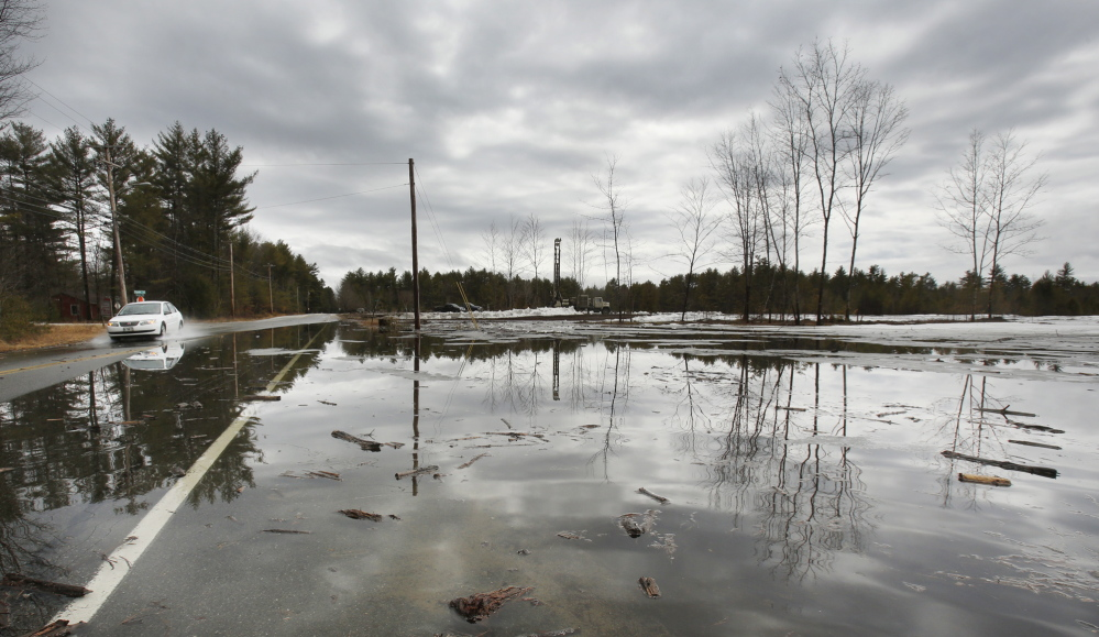 A car passes through a section of Route 113 in Standish that is covered by water near a low-lying field Tuesday.