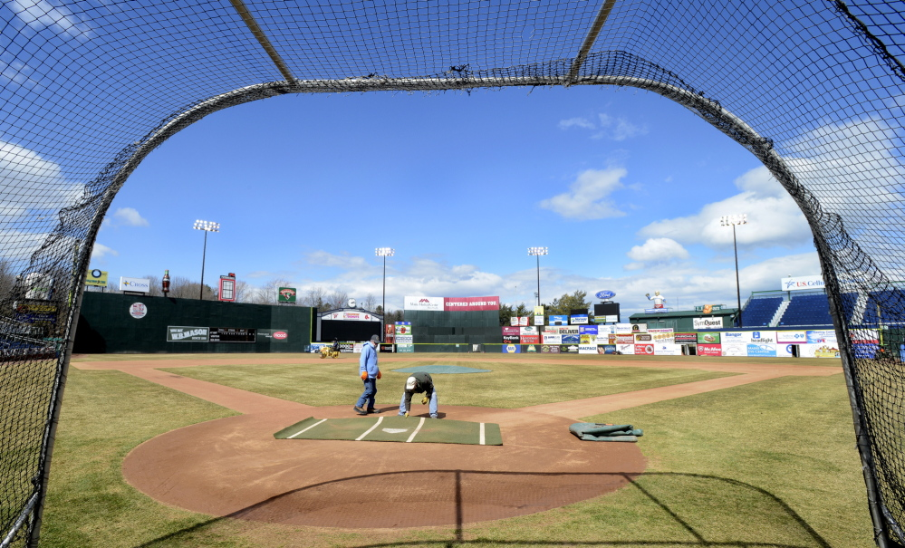 Framed by the batting cage, Steve Smith and Mike Diffin, members of the Portland Sea Dogs' grounds crew and staff, prepare Hadlock Field on Wednesday for tonight's home opener. The minor league team this season has plenty of top prospects, including pitcher Henry Owens, whose first start in Portland is set for Monday.