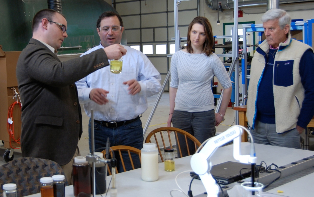 Scott Eaton, left, CTO for SeaChange Group, talks with Joe Migliaccio and Jessica Watson of the Maine Technology Institute and Sam Bishop, interim CEO of SeaChange, at the company's lab in Bucksport.