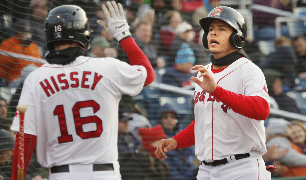Carlos Rivero of the Sea Dogs is met by teammate Peter Hissey after scoring on Matt Spring's double in the second inning, making it 1-1. Rivero went 3 for 4 with a double.